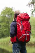 Man with red backpack hiking Stock Photos