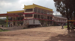 Person cleaning dirt road next to gas station in Maralal, Samburu, Kenya, Africa Stock Footage