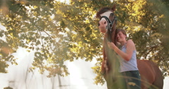 Vintage-style shot of a girl standing lovingly with her horse - stock footage