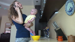 Mother talk phone and feed baby on hands with spoon. 4K Stock Footage