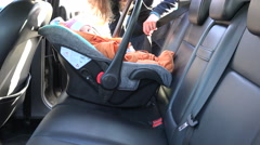Mother place baby safety chair in car back and fasten. 4K Stock Footage