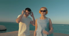 Man and woman getting pleasure from music on beach Stock Footage
