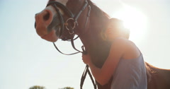 Girl smiling lovingly at her horse outdoors - stock footage