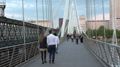 Pedestrians crossing on Hungerford Bridge Golden Jubilee Bridges London UK Stock Footage
