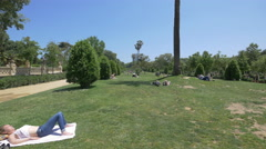 Relaxing on the grass in Ciutadella Park, Barcelona Stock Footage
