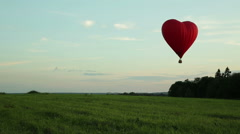 Hot air balloons flying over field in countryside Stock Footage