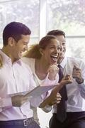 Office workers sharing lighthearted moment together - stock photo