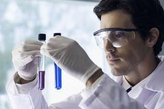 Scientist scrutinizing test tubes in lab - stock photo