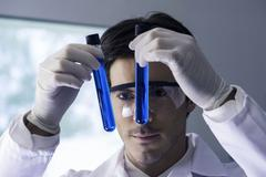 Researcher scrutinizing test tubes containing blue liquid in lab - stock photo