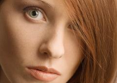 Woman's face and red hair covering one eye - stock photo