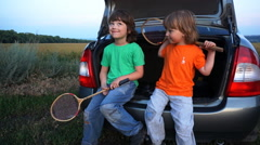 Two child photographed sitting in the trunk of a car trunk Stock Footage