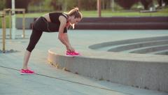 Stock Video Footage of Young woman tie shoes during sunset running