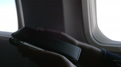 Typing sms on smart phone in the plane Stock Footage
