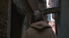 Woman in alleyway looking around Stock Footage