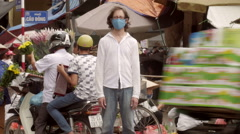 Time-lapse of man standing still at a busy market as the world whizzes by him Stock Footage