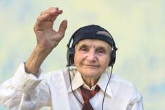 Stock Photo of Happy elderly woman with headphones listening to music.