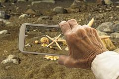 Stock Photo of Old hand takes a picture of starfish and sea shells on smart phone.