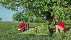 Couple of tourists set up the tent in the field under tree Stock Footage