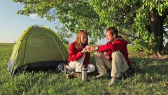 Couple of tourists drink tea near tent under big green tree Stock Footage