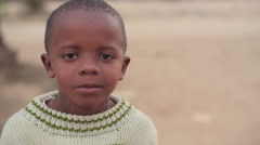 Cute small African boy chewing gum, Kenya, Africa, close up, shallow DOF Stock Footage