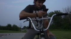 BMXer playing on phone at dusk - stock footage