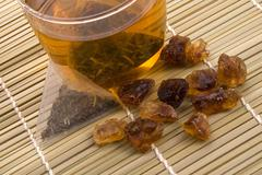 white tea, nylon tea-bag and golden sugar - stock photo
