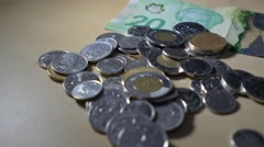 Canadian coins ontop of bills Stock Footage