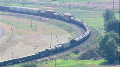 AERIAL United States-Freight Train Approaching Bend In Clark Fork River Stock Footage