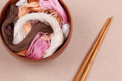 Cross-stitch threads in bowl - stock photo