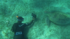 Diver with camera shooting sea turtle Stock Footage