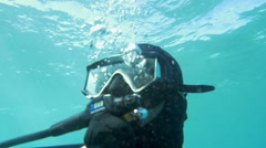 Scuba diver in blue water on sunny day Stock Footage