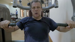 Sweaty man working out on exercise machine Stock Footage