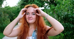 Portrait of a beautiful redhead girl in the spring garden happy Stock Footage