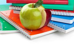 School supplies and green apple in foreground. Stock Photos