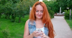 Redhead Texting on a smartphone. Women working with phablet outdoors Stock Footage