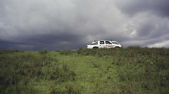 Toyota cars on grassy hill with cloudy storm in sky Stock Footage