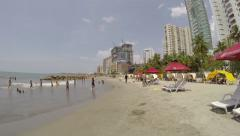 People in beach close to hotels Stock Footage