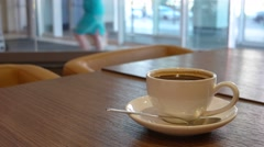 Cup of americano coffee on a wooden table with glass of water Stock Footage