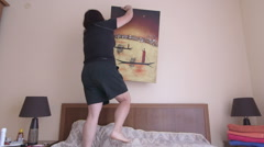 Woman hanging picture frame on the wall at home Stock Footage
