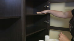 Woman cleaning kitchen cupboard wiping shelf Stock Footage