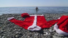 Santa Claus suit costume on the beach man walking into sea Stock Footage
