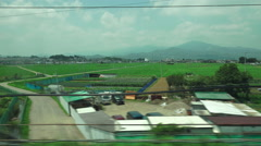 Passing Thru Japanese Countryside Mountain In Distance On Fast High Speed Bul - stock footage