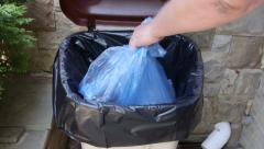 Hand putting plastic garbage bag into waste bin container - stock footage