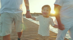 Happy boy walking with grandparents along the pier at sunset - stock footage