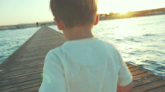 Little boy running on the pier at sunset - stock footage