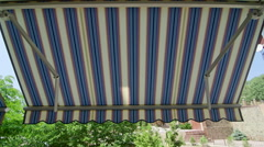 Folding retractable awning mounted onto the outside wall of house Stock Footage