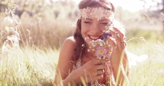 Smiling hippie girl in a park holding wild flowers Stock Footage