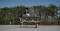 skateboarder picnic table jump - stock footage