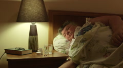 Obese old woman in bed taking pills on bedside table Stock Footage