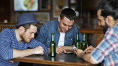 Male friends with smartphones drinking beer at bar Stock Footage